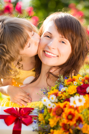 Woman and child with bouquet of flowers against green background. Spring family holiday concept. Mother`s day Stock Photo - 26108899