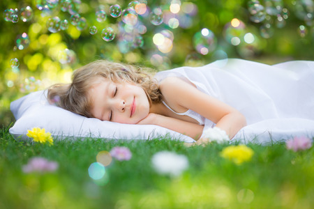 Happy kid sleeping on green grass outdoors in spring garden photo