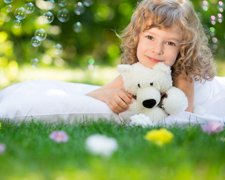 Happy child with toy teddy bear on green grass outdoors in spring garden Stock Photo - 26109539