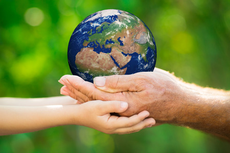 Child and senior man holding Earth in hands against green spring background.