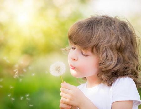niños felices: Niño feliz que sopla el diente de león al aire libre en el parque de la primavera Foto de archivo