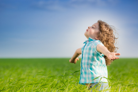 Happy kid with raised arms in green spring field against blue sky. Freedom and happiness concept 免版税图像