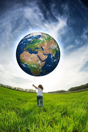 Niño que sostiene la Tierra en la mano contra el cielo azul y el campo verde primavera. Foto de archivo