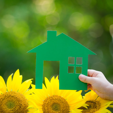 Paper house in hand against spring green background. Real estate concept