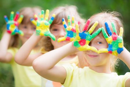 Gelukkig kind met geschilderde handen tegen de groene voorjaar achtergrond