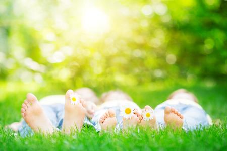Familie liggend op gras in openlucht in het voorjaar park Stockfoto