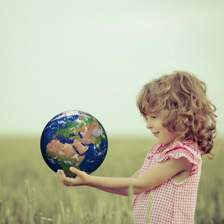 Dítě drží Zemi v ruce proti zelené jaře pozadí.
