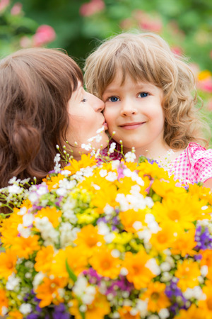Woman and child with bouquet of flowers against green background. Spring family holiday concept. Mother's day photo