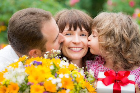 Happy family with bouquet of flowers against green background. Spring holiday concept. Mothers day photo
