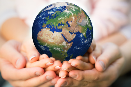 mundo manos: Familia que sostienen la tierra en las manos.
