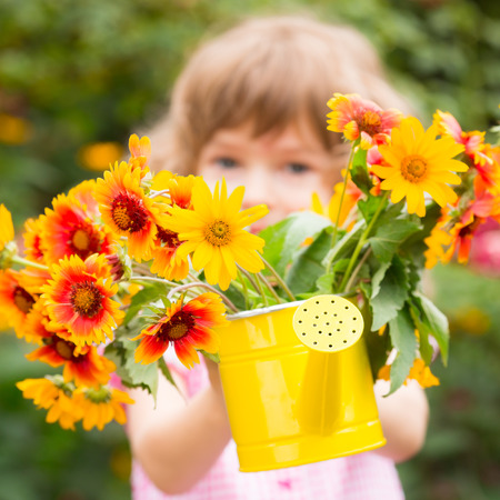 Child with bouquet of flowers against green background. Spring family holiday concept. Mother's day photo