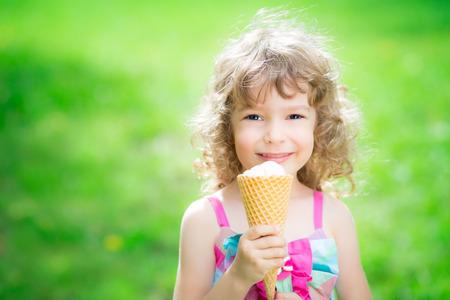 child ice cream: Happy child eating ice cream outdoors in summer park