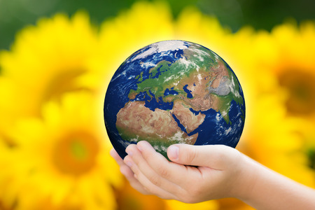 Child holding Earth in hands against green spring background. photo