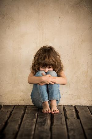 Enfant triste Siiting sur le sol dans une pièce sombre Banque d'images