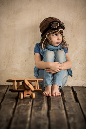 Sad child with toy wooden airplane sitting on the floor photo