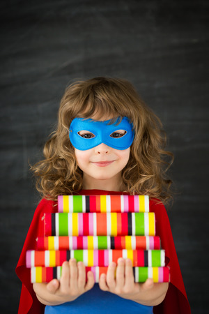 Superhero kid in class against blackboard photo