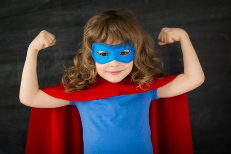 Chico super héroe contra la pizarra de la escuela