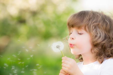 al�rgico: Ni�o feliz que sopla el diente de le�n al aire libre en el parque de la primavera Foto de archivo