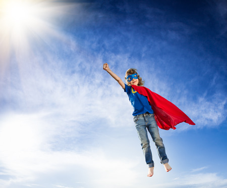dramatic: Superhero kid flying against dramatic blue sky background