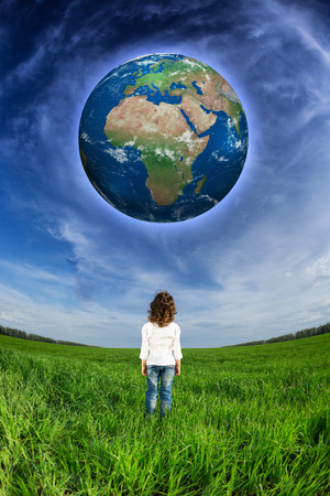 Child looking at the Earth planet against blue sky and spring green field.  photo