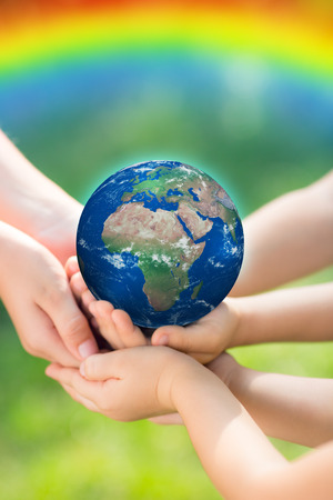 Children holding Earth in hands against green spring background.