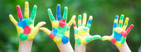 Colorful painted hands against green spring background Stock Photo