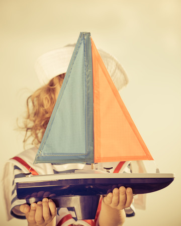 Happy kid playing with toy sailing boat against blue sky background photo