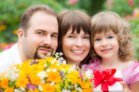 Happy family with bouquet of flowers against green background photo