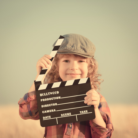 Child holding clapperboard against summer sky background photo