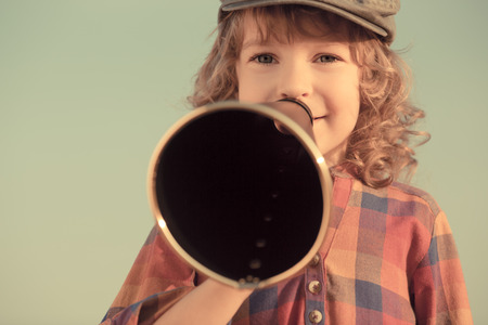 Kid shouting through vintage megaphone photo
