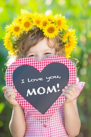 Child holding blackboard written i love you mom against green background