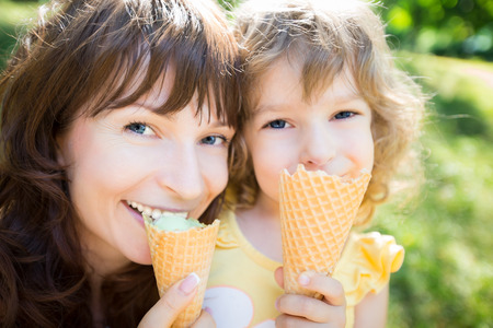 ice cream woman: Happy child and mother eating ice cream outdoors in summer park