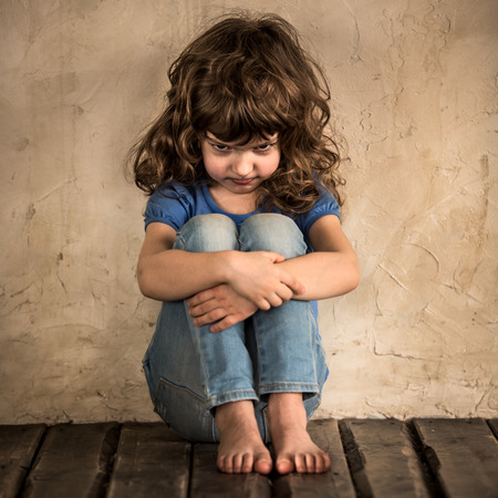 Sad child siiting on the floor in dark room Stock Photo