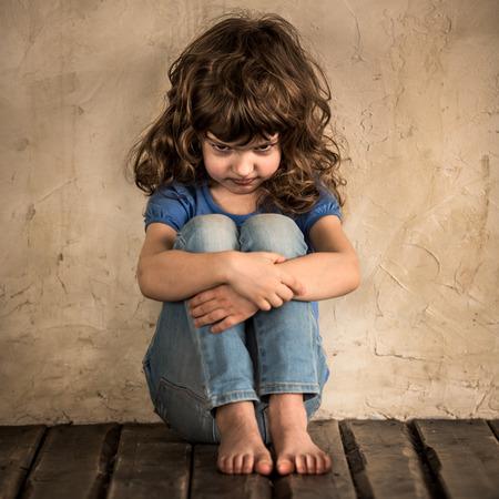 Sad child siiting on the floor in dark room Standard-Bild