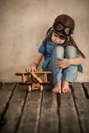 Sad child playing with toy wooden airplane photo