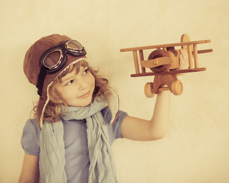 Happy kid playing with toy wooden airplane indoors photo