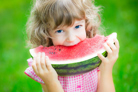 children eating: Happy child eating watermelon outdoors in summer park Stock Photo