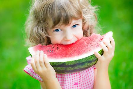 niños comiendo: Niño feliz comiendo sandía al aire libre en el parque de verano Foto de archivo