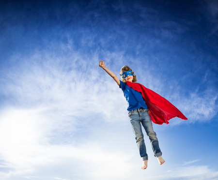 Superhero kid flying against dramatic blue sky background