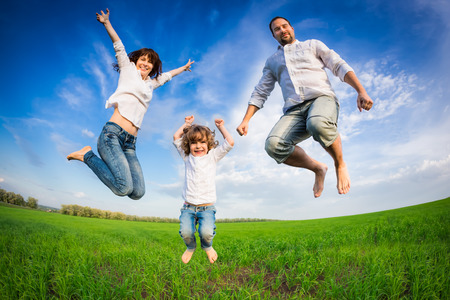 Happy family jumping in green field against blue sky. Summer vacation concept