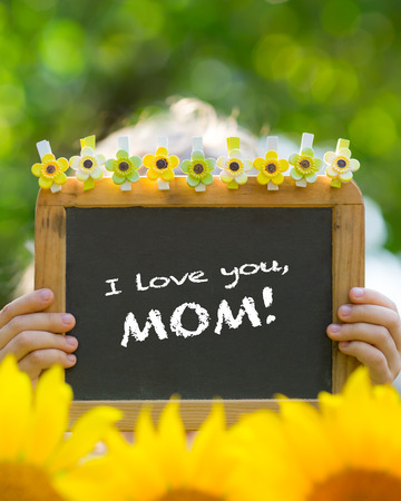 Child hold a board written i love you mom photo