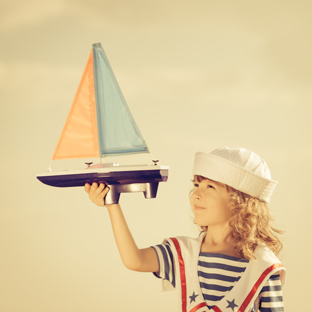 Happy kid playing with toy sailing boat against summer sky background. Travel and vacations concept