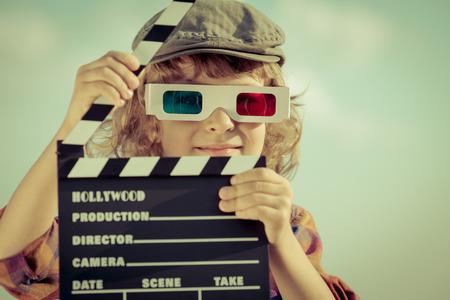 Kid bedrijf klepel board tegen de zomer hemel achtergrond. Cinema-concept