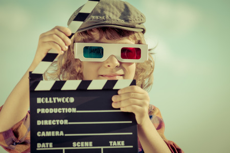 Kid holding clapper board against summer sky background. Cinema concept
