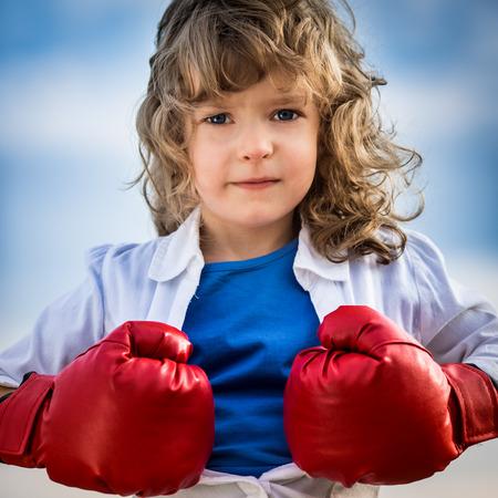 feminism: Kid opening his shirt like a superhero. Girl power and feminism concept Stock Photo