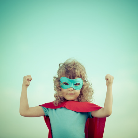 Superhero kid against summer sky background. Girl power and feminism concept photo