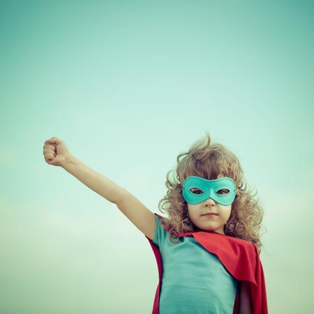 여름 하늘 배경에 슈퍼 히어로 아이입니다. 소녀 파워와 페미니즘 개념 스톡 콘텐츠