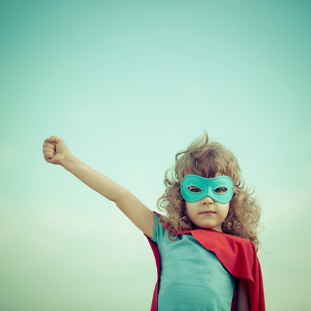 power: Superhero kid against summer sky background. Girl power and feminism concept