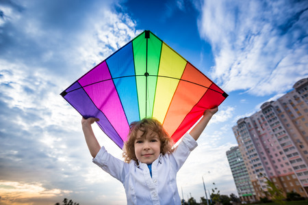 Kid flying a kite against dramatic blue sky background photo