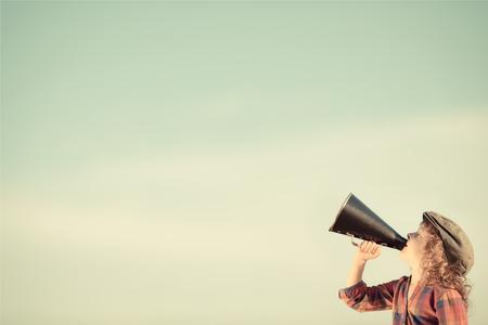 komunikacja: Dzieciak krzycząc przez zabytkowe megafon. Koncepcja komunikacji. W stylu retro